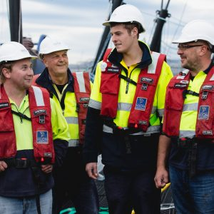 Four male employees on a pen in life jackets and hard-hats